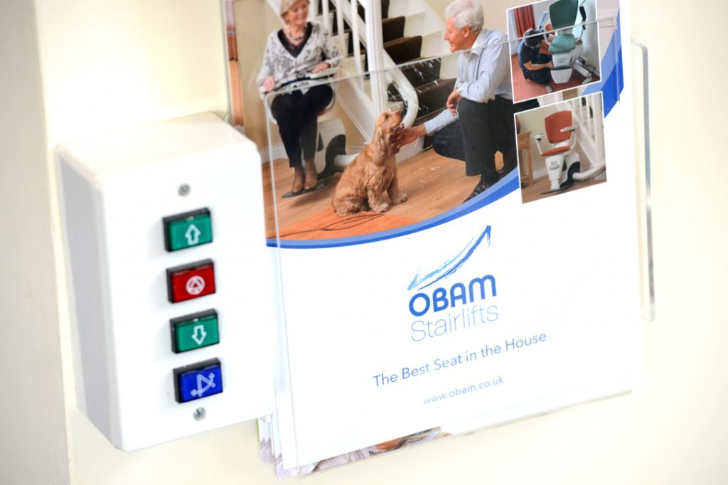 Obam Stairlifts brochure on display next to stairlift controls