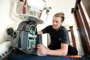 Picture of an engineer installing a stairlift