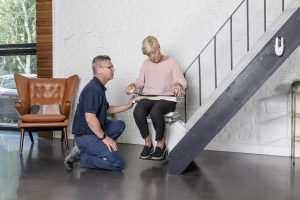 Picture of installer showing client how to use their newly installed Handicare 1100 Stairlift